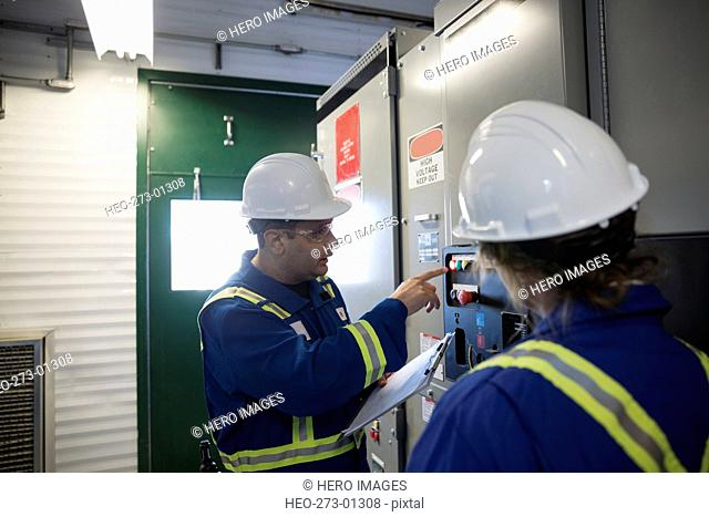 Workers discussing control panel in gas plant