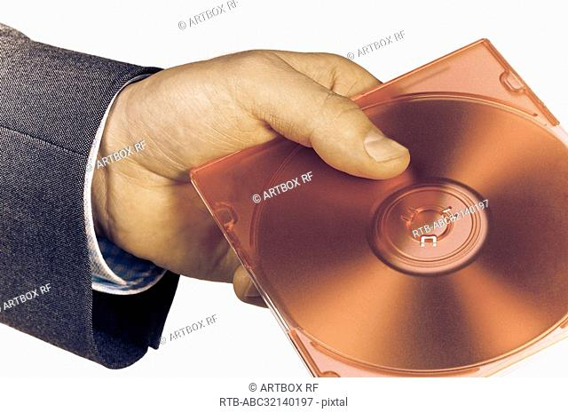 Close-up of a businessman's hand holding a compact disc