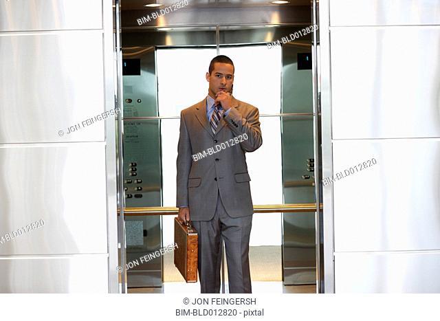 Young businessman inside elevator