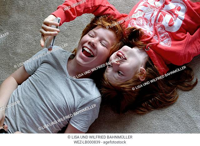 Portrait of brother and sister lying on the floor taking selfies with smartphone