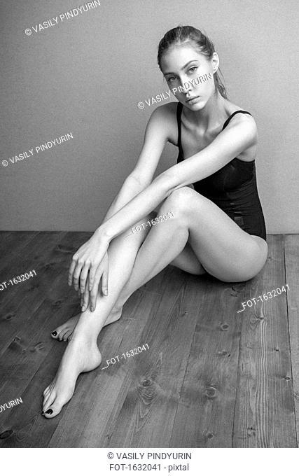 Portrait of confident woman wearing leotard sitting on hardwood floor against wall