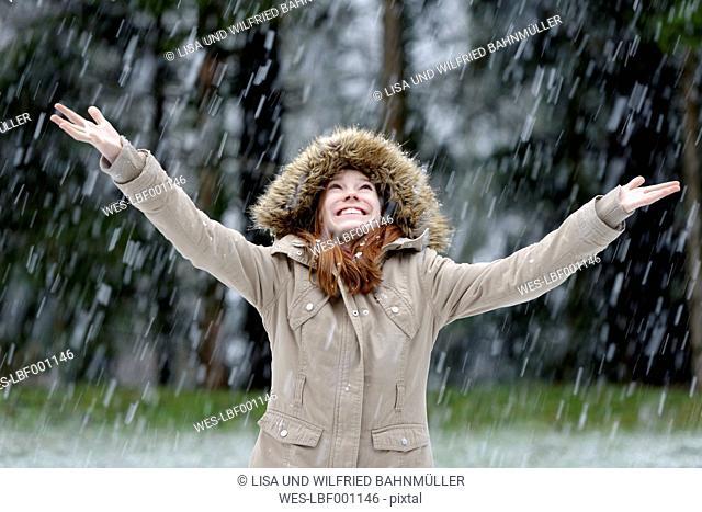 Girl enjoying snow fall, beginning of winter