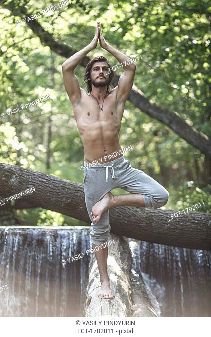 Young man standing in tree pose on log against waterfall at forest