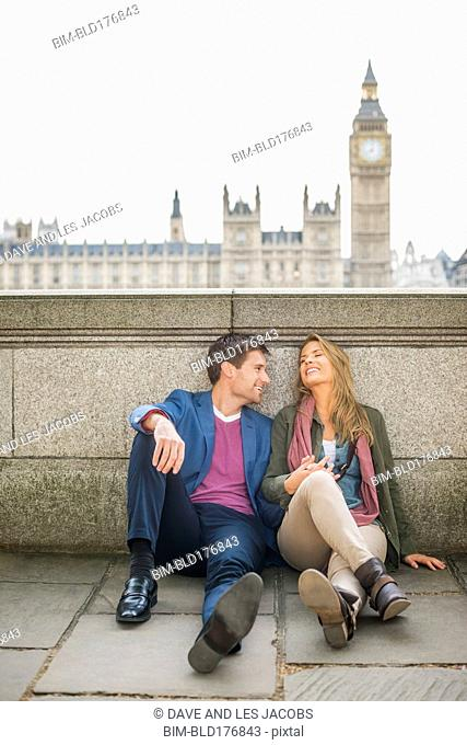 Caucasian couple talking at clock tower, London, Middlesex, United Kingdom