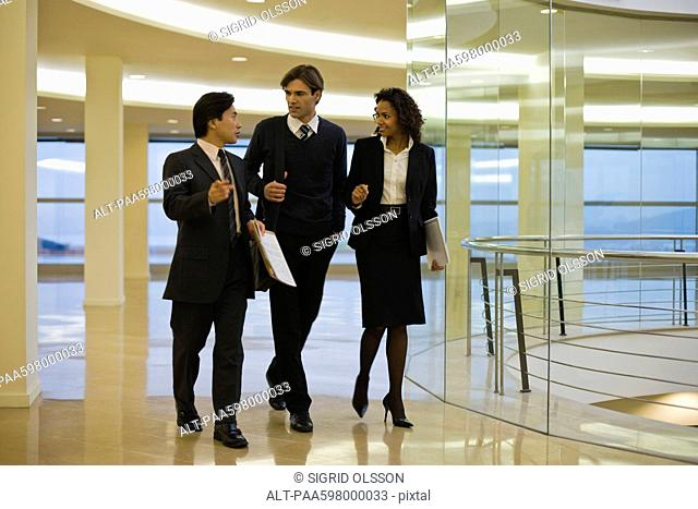 Business executives walking and talking together in building