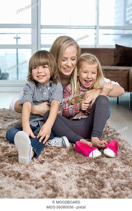 Playful mother with children sitting on rug in living room