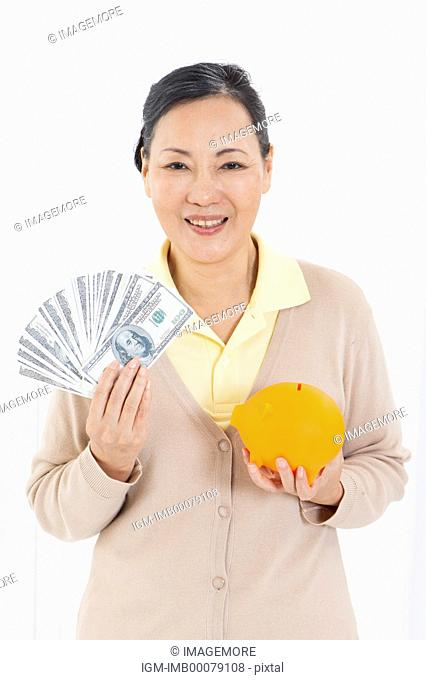Senior woman holding paper money and piggy bank with smile