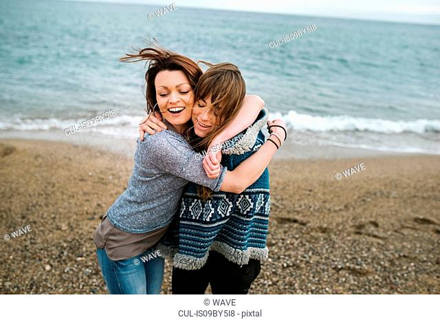 Two young adult female friends hugging on beach, Barcelona, Spain
