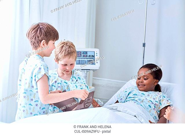 Boy patients using blood pressure cuff on friend in bed on hospital children's ward