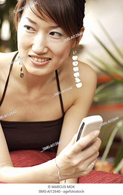 Young woman with mobile phone, looking away