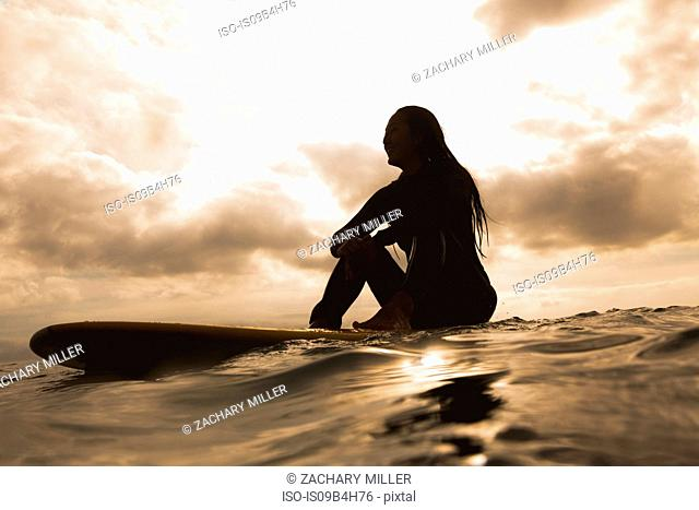 Young woman in sea, sitting on surfboard