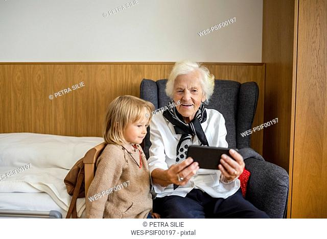 Portrait of aged woman watching together with her great-granddaughter photos on smartphone