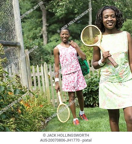 Two mid adult women holding tennis rackets and walking in a lawn