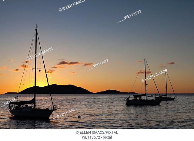Silhouette of sailboats moored in water with orange glow of sunset lighting up the clouds and sky in Caribbean
