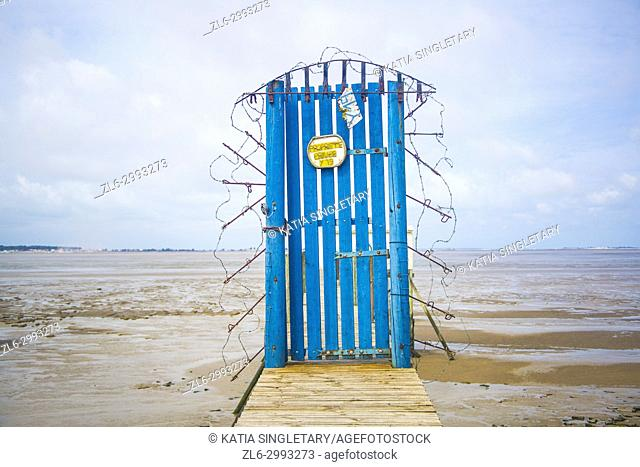 Bright blue door in the middle of a pier with barb wire. Very compelling emotion and concept of Hell. Tide is down, water is brown