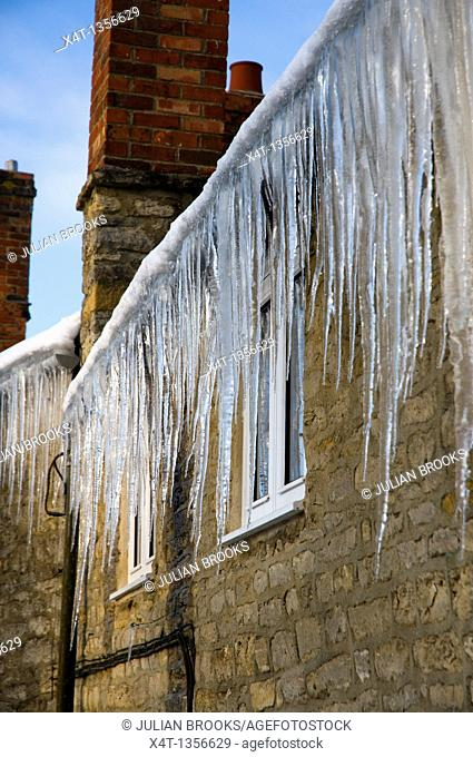 long dangerous icicles hanging from a roof in Oxfordshire, winter