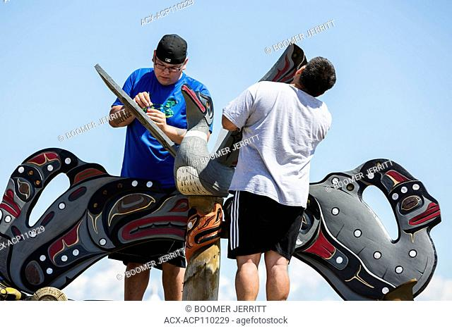 Family members refurbish a mortuary pole at the gravesite of a family member. Campbell River, Vancouver Island, British Columbia, Canada
