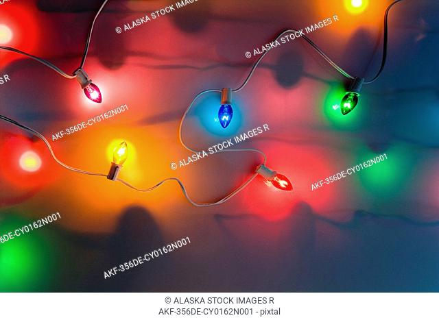 One strand of multi-colored large Christmas tree lights glowing on dimmed white background studio portrait