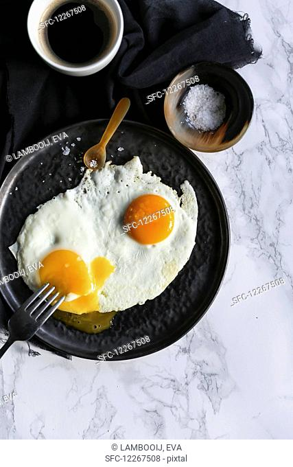 A fried egg with salt and a cup of coffee