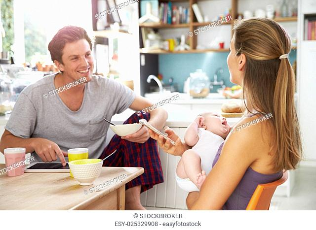 Family With Baby Girl Use Digital Devices At Breakfast Table