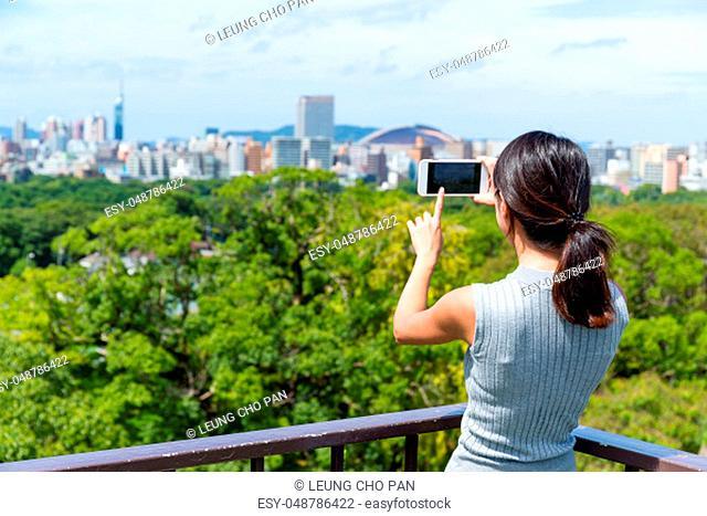 Woman taking photo on cellphone in Fukuoka city