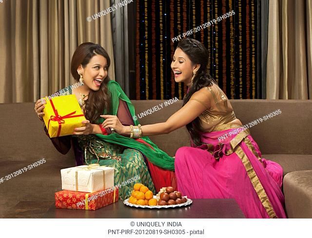 Female friends playing with gifts on Diwali