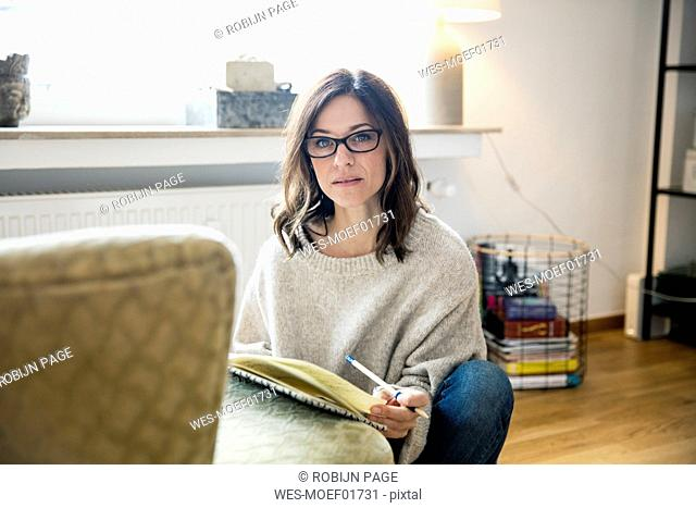 Woman sitting on floor, journalising in her diary