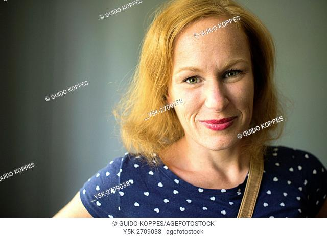 Tilburg, Netherlands. Studio-portrait of a red-haired woman