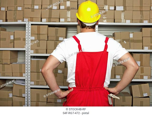 Warehouseman standing in front of a shelf with a lot of goods in it