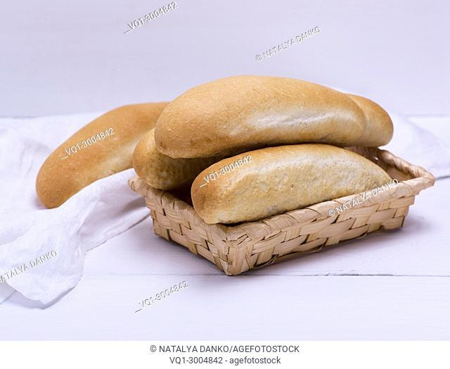 buns of white wheat flour in a wicker basket on a white wooden background