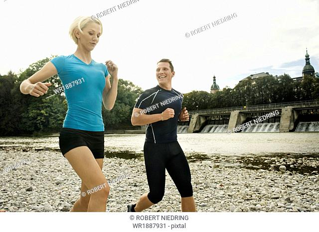 Young couple jogging on the waterfront, Munich, Bavaria, Germany
