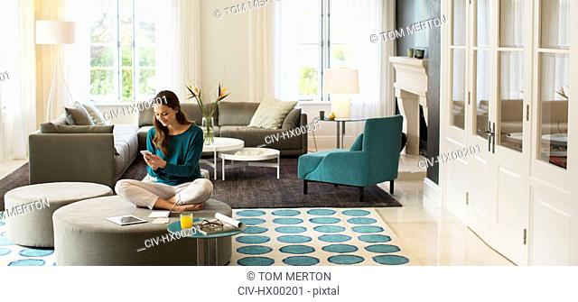 Woman texting on cell phone on ottoman in living room