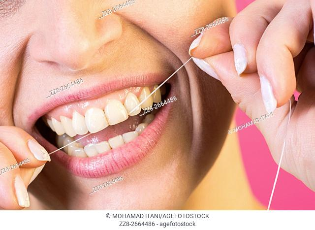 Close up of a woman flossing her teeth