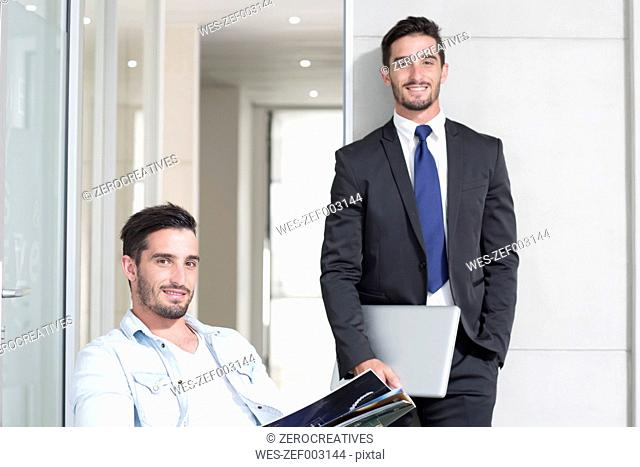 Casually and formally dressed twin males in office