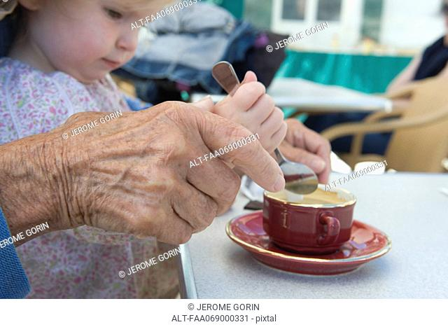 Toddler girl helping grandmother stir cup of coffee, cropped