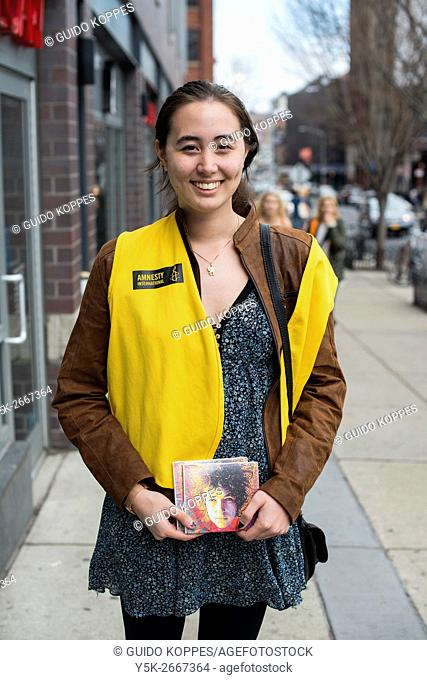 New York City, USA. Young attractive and miling woman promoting Amnesty International in the streets of down town Brooklyn