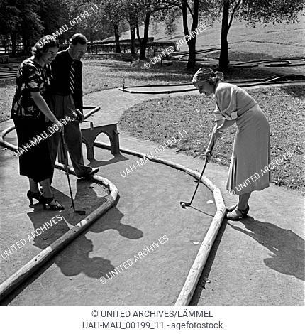 Zwei Frauen und ein Mann spielen Minigolf, Deutschland 1930er Jahre. Twi women and a man playing crazy golf, Germany 1930s
