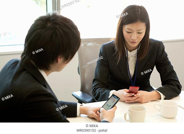 Young businessman and businesswoman using mobile phone at desk