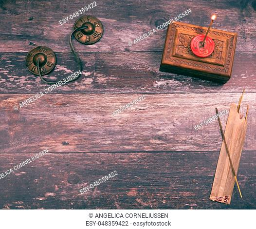 Burning a mystical incense stick in a mindfullness ritual to get a spiritual and peaceful meditation, with copyspace on wood background