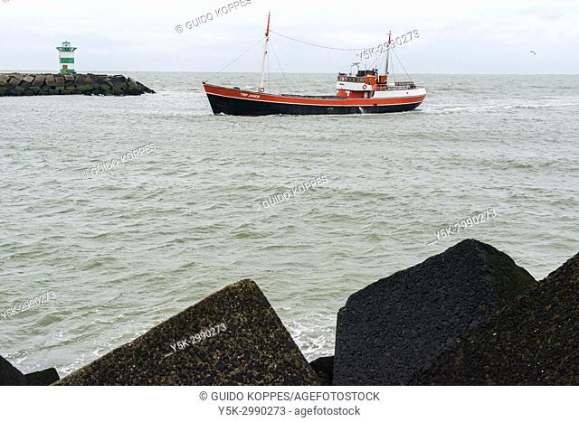 Scheveningen, Netherlands. Little fishing ship entering the harbor after a fishing trip. The harbor is mail dedicated to fishing and fishing boats from the...