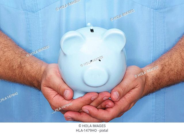 Mid section view of a male nurse holding a piggy bank