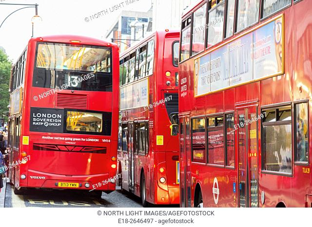 UK, England, London. Oxford Street. Several London transit buses block the way on busy shopping street