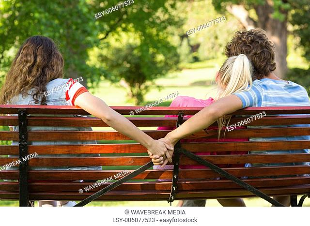 Man with girlfriend while holding hands with another woman