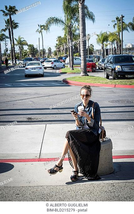 Caucasian woman sitting on concrete barrier in parking lot