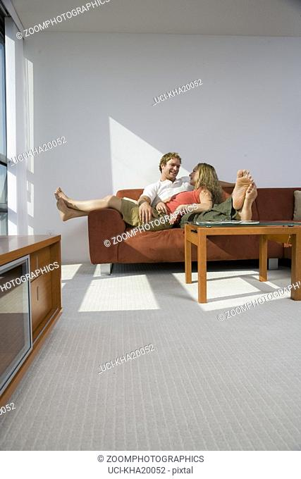 Couple on sofa with woman's feet hanging off side