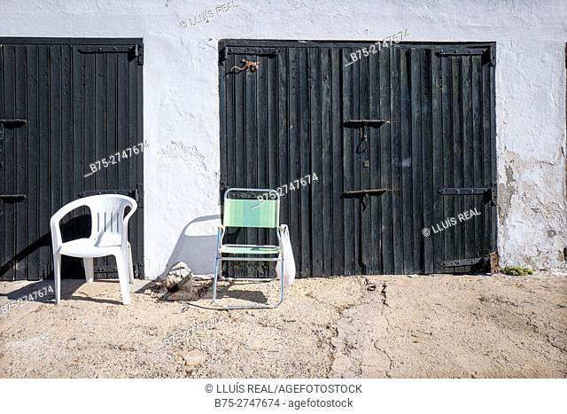 Garage doors and chairs. Cala Biniancolla. Minorca, Balearic Islands, Spain