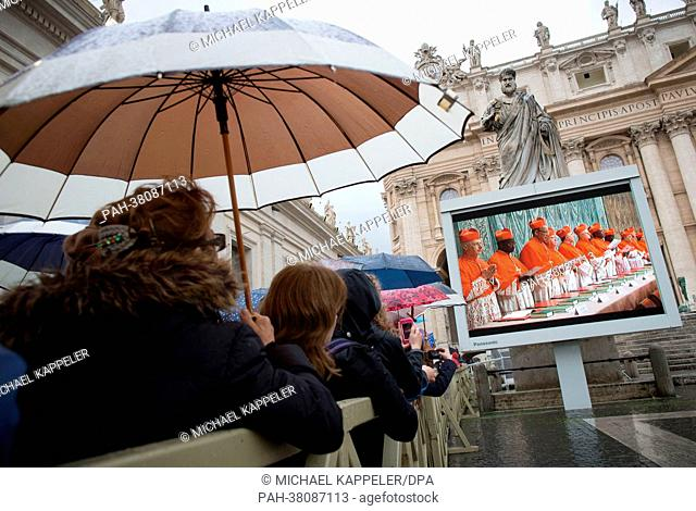 Pilgrims watch the entrance of the Cardinals into the Sistine Chapel on video monitors on St. Peter's Square in Vatican City, Vatican, 12 March 2013