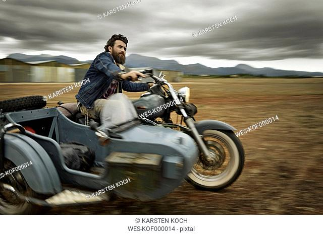 Man with full beard driving motorcycle with sidecar