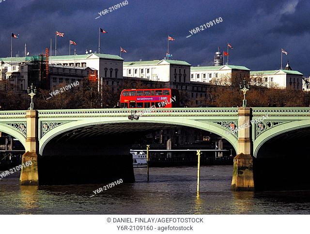Westminster Bridge on a day of mixed and moody light in the heart of London, England. A red double-decker bus is in the foreground and the British Ministry of...