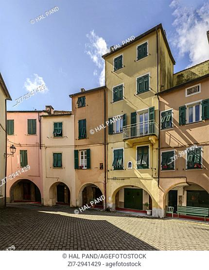 foreshortening of little round square among old picturesque bending houses with covered walkway, shot in bright late summer light at Varese Ligure, Genova